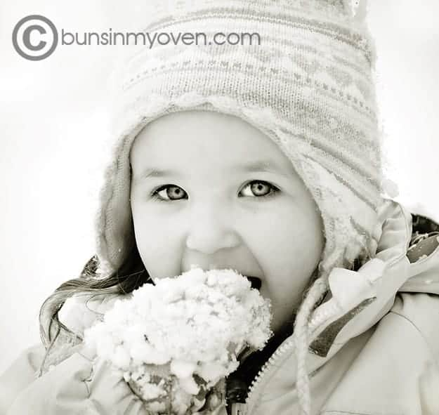A little girl that is eating snow.