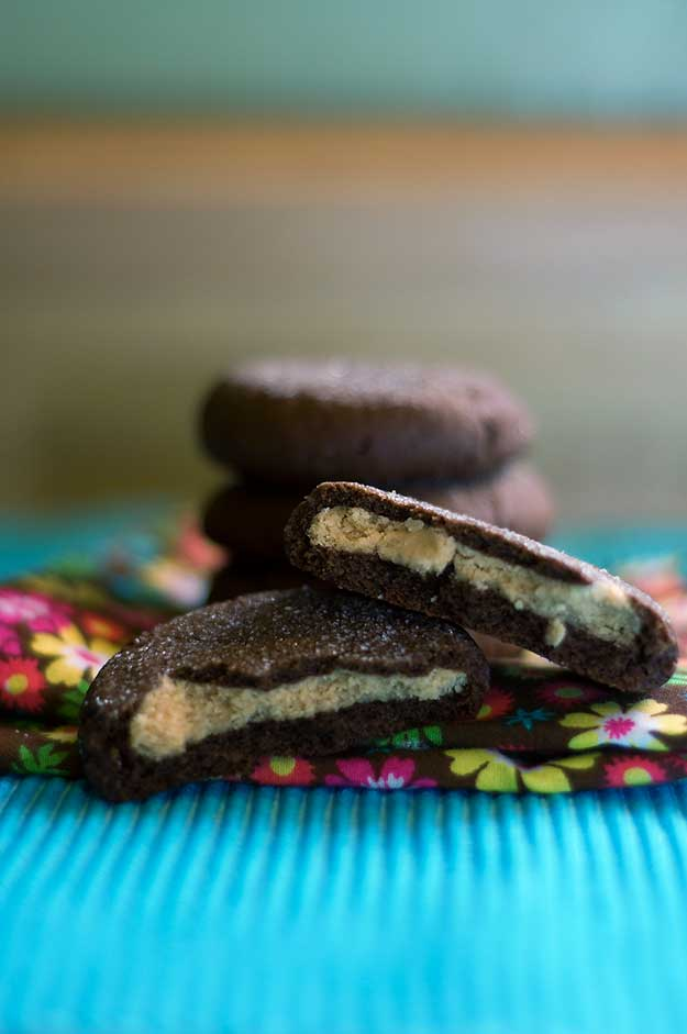 Two peanut butter filled chocolate cookies on a flower cloth napkin