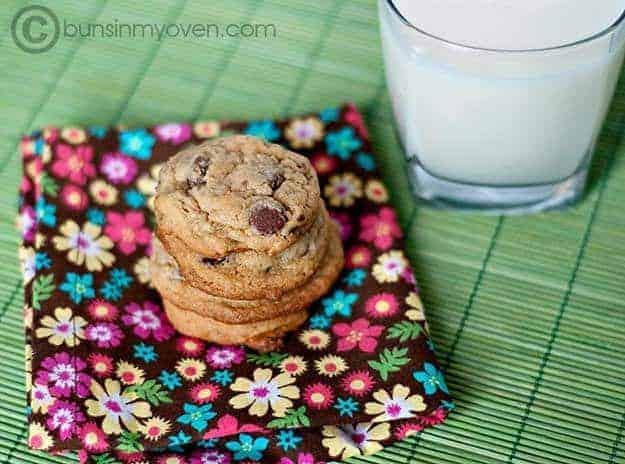 Three chocolate chip cookies on a placemat with a glass of milk.