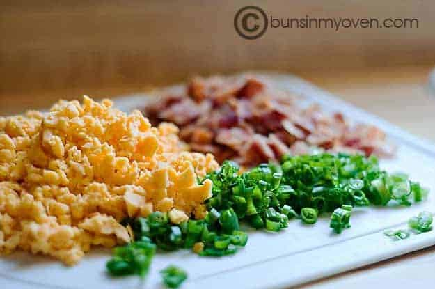 Pieces of chives and bacon on a cutting board