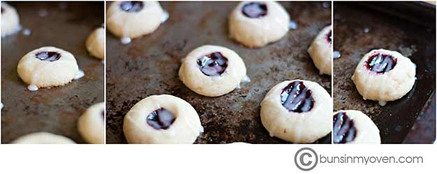 Several thumbprints with raspberry filling on a baking sheet.