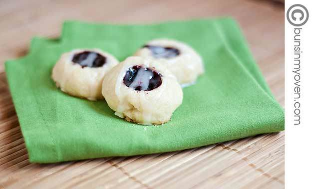 Three raspberry thumbprint cookies on a folded cloth napkin.