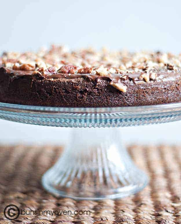 brownie cake on a clear glass cake stand