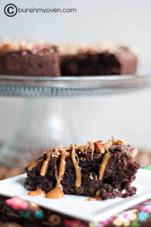 A closeup of a piece of brownie cake in front of a cake stand