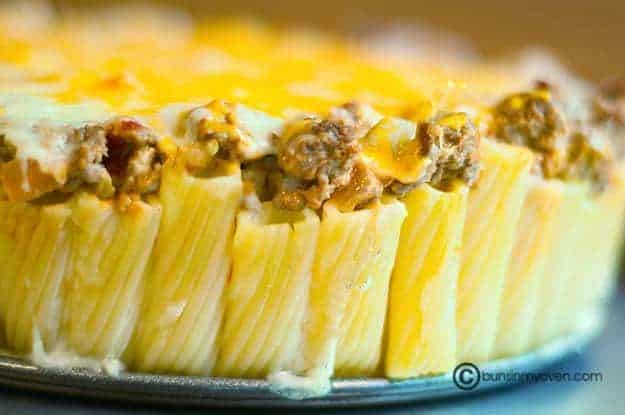 Standing pasta noodles topped with ground beef and cheese