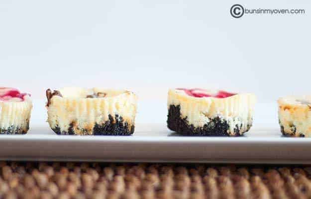 Two cheesecake muffins on a baking sheet.