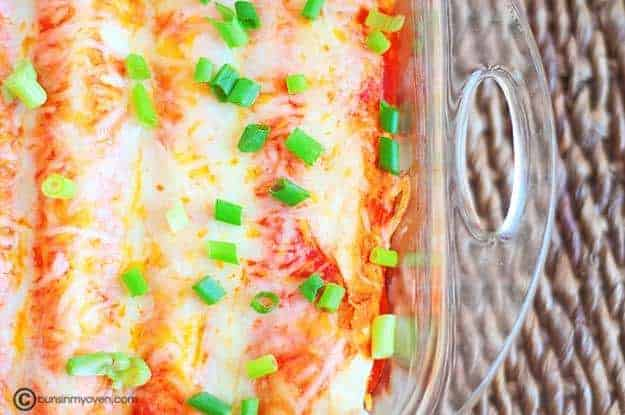 An overhead view of cheesy enchiladas in a clear glass baking pan