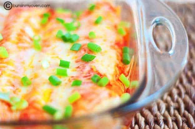 cheesy enchiladas in a clear glass baking pan