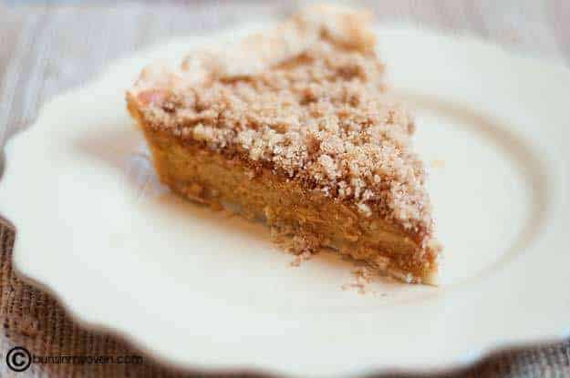A piece of pumpkin pie with crushed walnut on top.