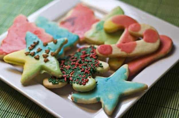 Several Christmas cookies on a square plate.
