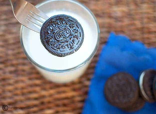 An Oreo that was dipped in milk of the above a glass