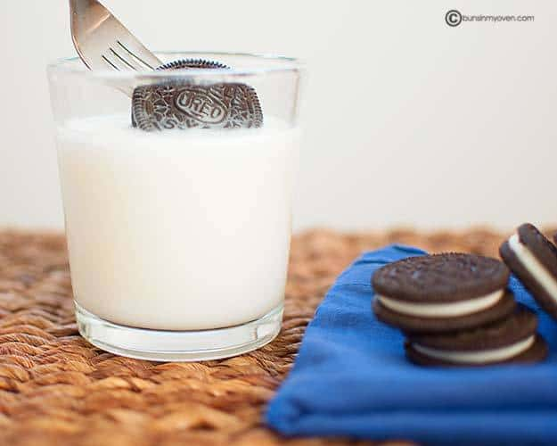 An Oreo on a fork being duped into milk