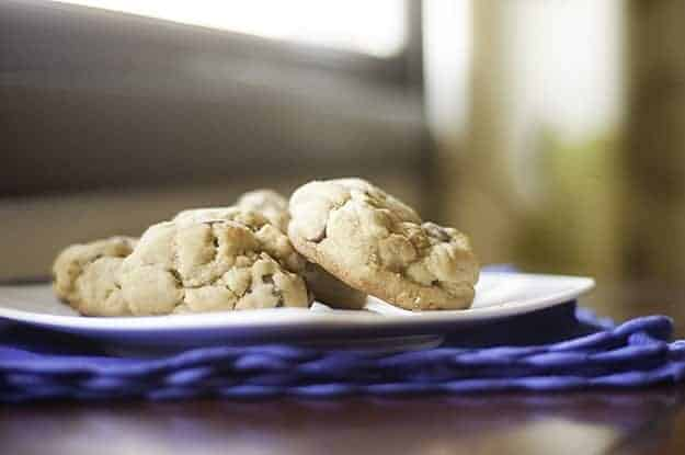 Puffy chocolate chip cookies on a plate.