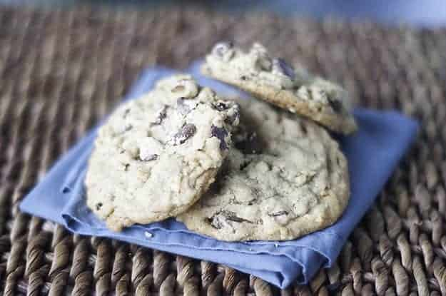 Three chocolate chip cookies on a blue cloth napkin