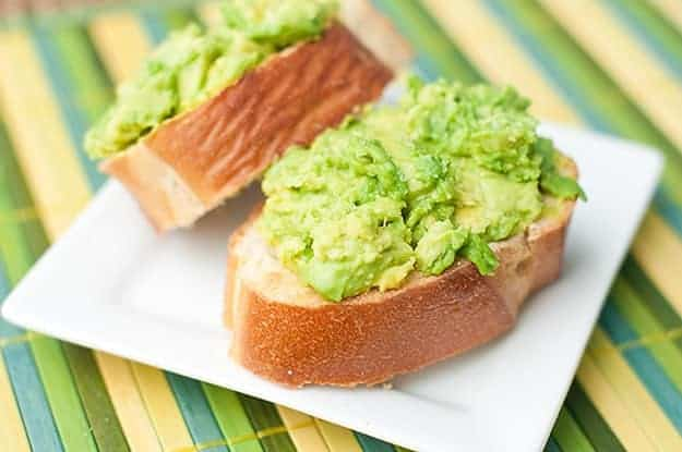 A close up of two slices of avocado toast