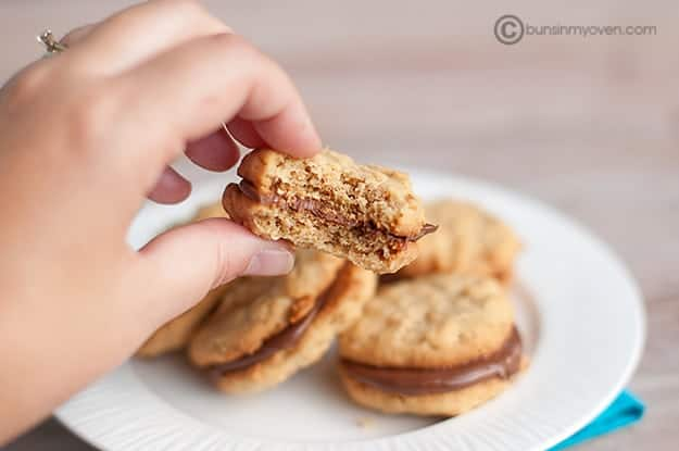 A person holding up a peanut butter sandwich cookie with a bite taken out of it.