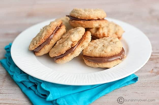 Several sandwich cookies on a white plate