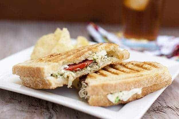 Chicken pesto sandwich with chips.