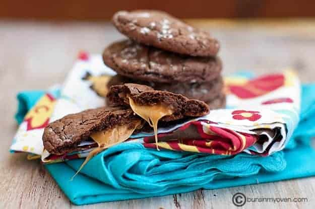 A stack of chocolate cookies behind a cookie split in half showing caramel in the middle.