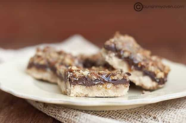 A caramel pecan shortbread square on a plate in front of more shortbread pieces