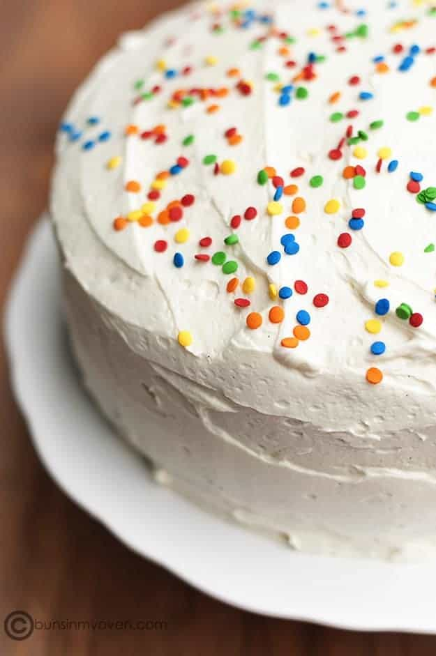 Whipped frosting on a cake with confetti sprinkles.