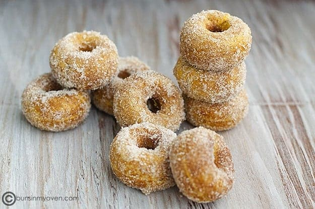 Stacked pumpkin donuts on a table.