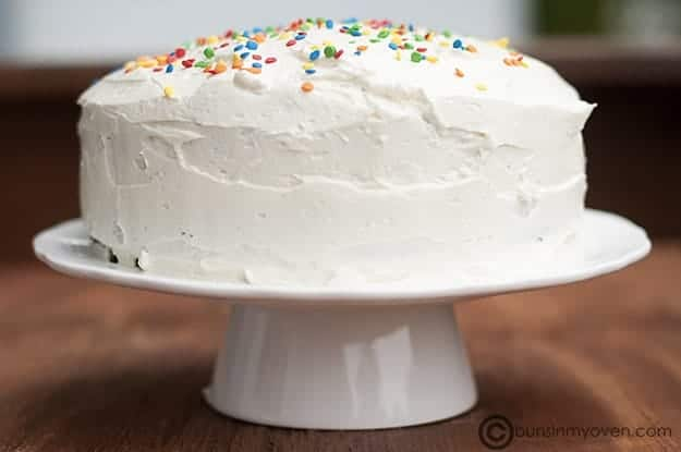 Whipped icing on a round cake with confetti sprinkles.