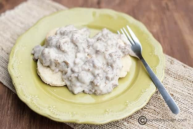 Homemade sausage gravy on green plate.
