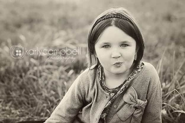 Black and white photo of a girl in sitting in the grass.