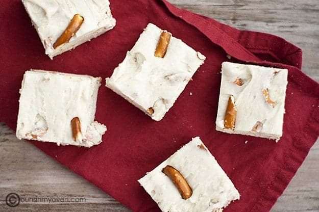 Five chunks of white chocolate fudge with pretzels on a folded napkin
