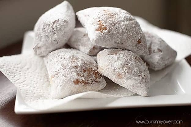 Six Beignets on a white square dish.