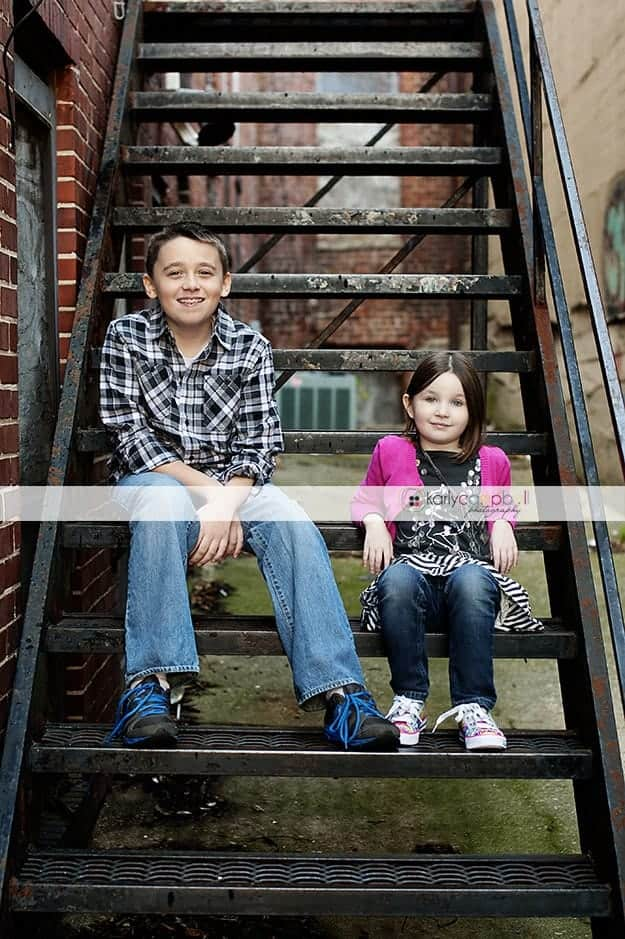 Two gids sitting on metal stairs in an alley