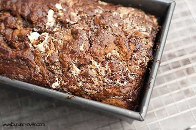 A bread pan with a loaf of banana bread in it.