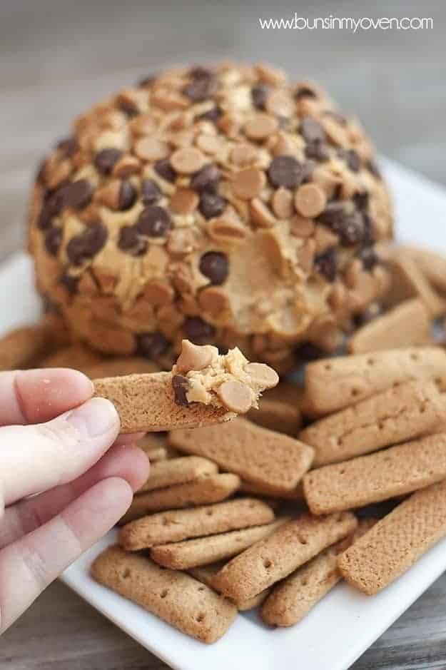 A person holding up a cookie with a scoop of a peanut butter cheese ball on it.