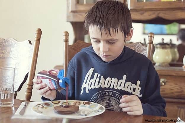 A boy sitting at a table pouring syrup on a pancake
