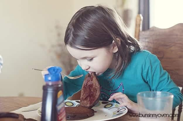 A whole pancake in a young girl\'s mouth.