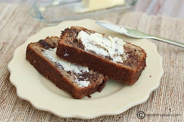 Two slices of banana bread with butter spread on top.