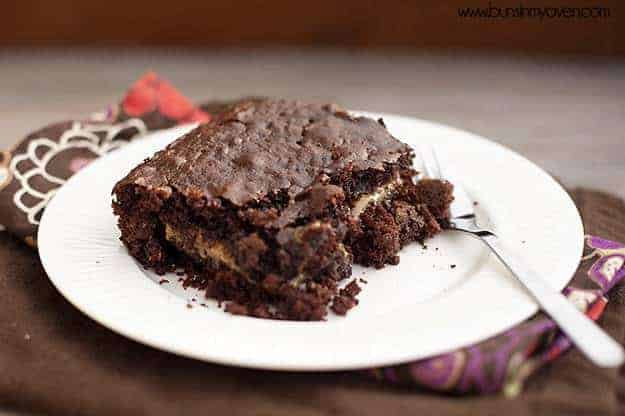 A close up of a gooey chocolate cake on a whtie plate