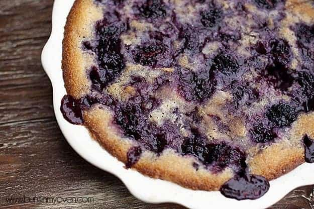 A close up of a pie plate full of blackberry cobbler.