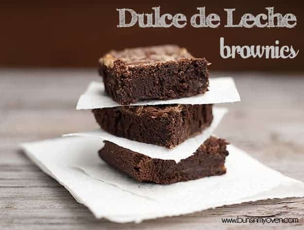 A side view of three stacked brownies separated by paper napkins