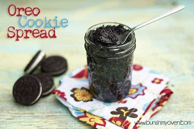 A jar of oreo spread on a table next to a pile of Oreos.