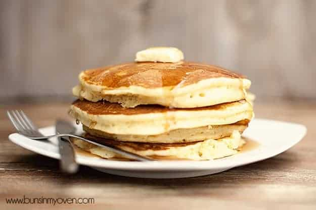 A side view of a stack of pancakes topped with butter