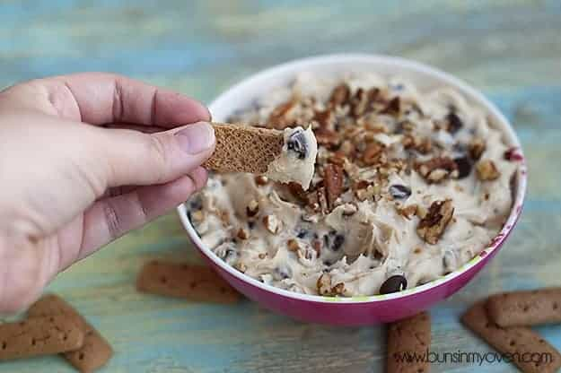 The person dipping cookies into chocolate chip cookie dough dip