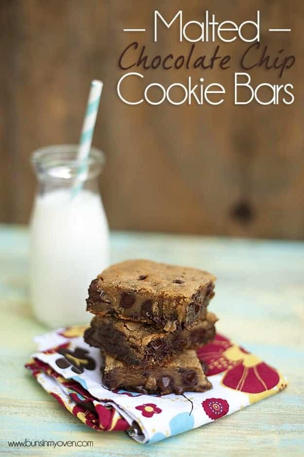 Three chocolate chip cookie bars in front of a milk jar