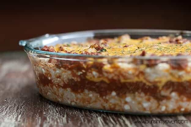 Looking through a clear glass pan at a layer of rice ground beef and cheese