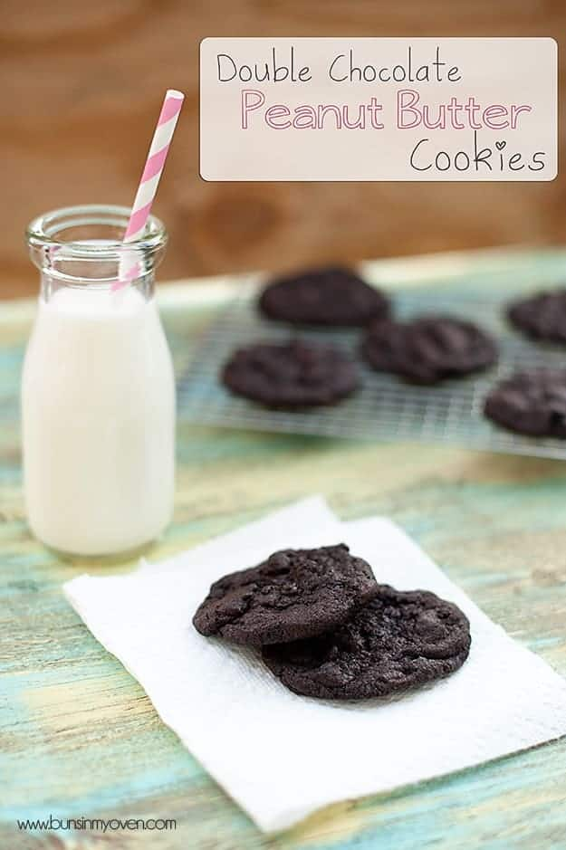Two chocolate cookies on a napkin in front of a jar of milk with a straw in it.