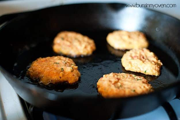 Corn cakes cooking in a cast iron skillet