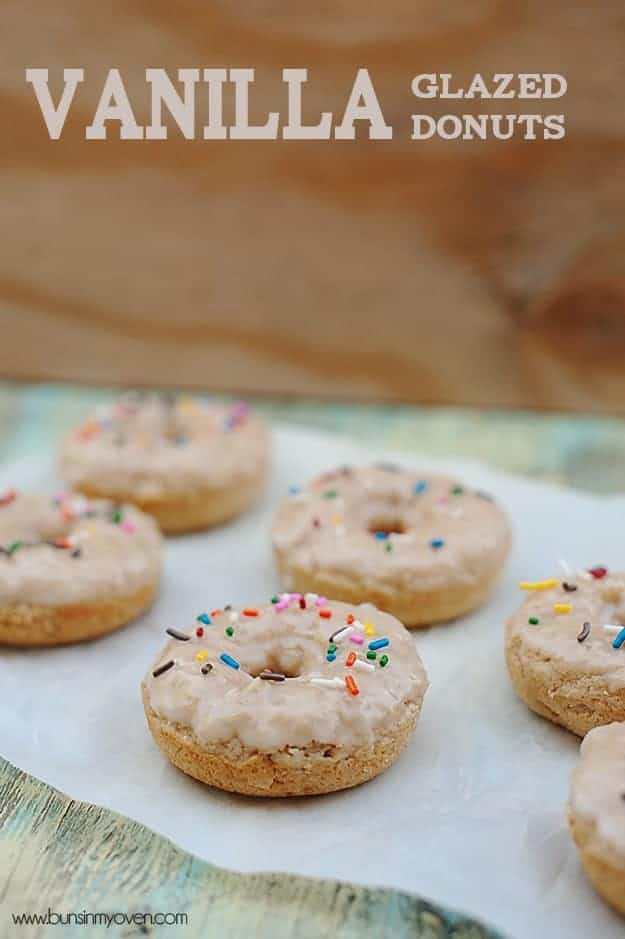Several vanilla donuts spread out on a table