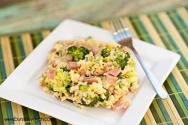 A close up of a plate of broccoli and diced ham with a fork in it.