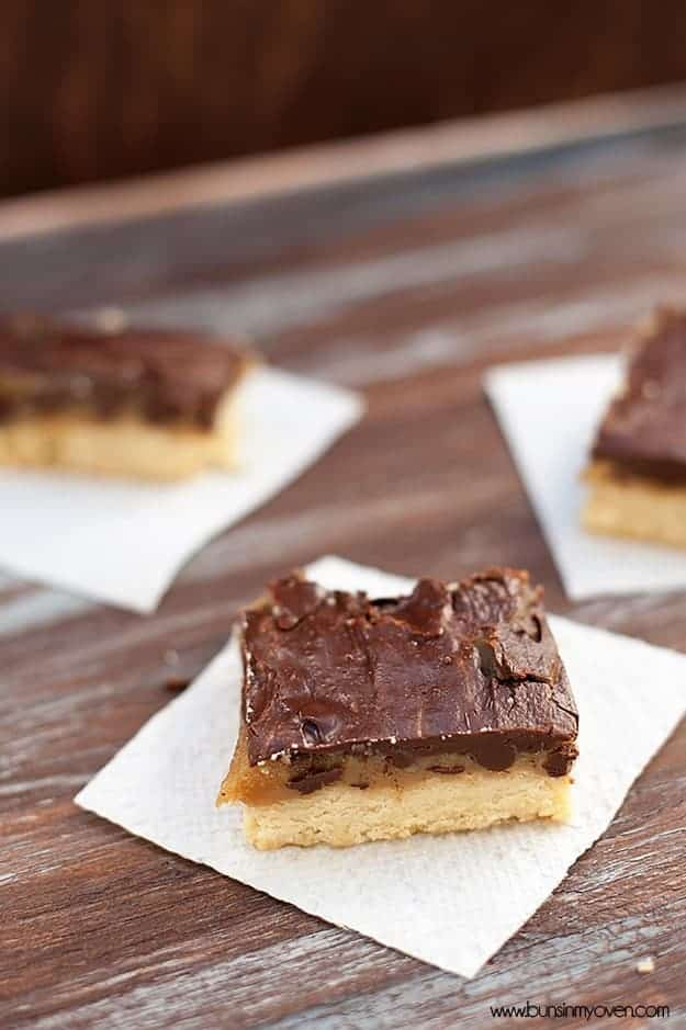 A few shortbread bars topped with caramel and chocolate on a table.